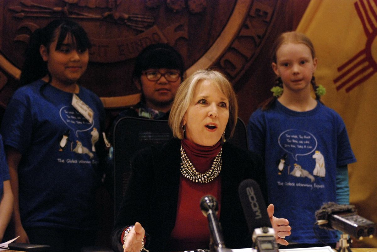 New Mexico Gov. Michelle Lujan Grisham, center, signs an executive order for state agencies to aggressive pursue strategies to reduce greenhouse gas emissions on Tuesday, Jan. 29, 2019, in Santa Fe, N.M. flanked by student activists on global warming issu