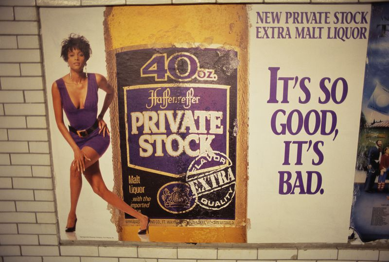 """A malt liquor ad hanging on a subway wall, with a photo of a woman in a low-cut dress, a bottle, and the tagline """"IT'S SO GOOD, IT'S BAD."""""""