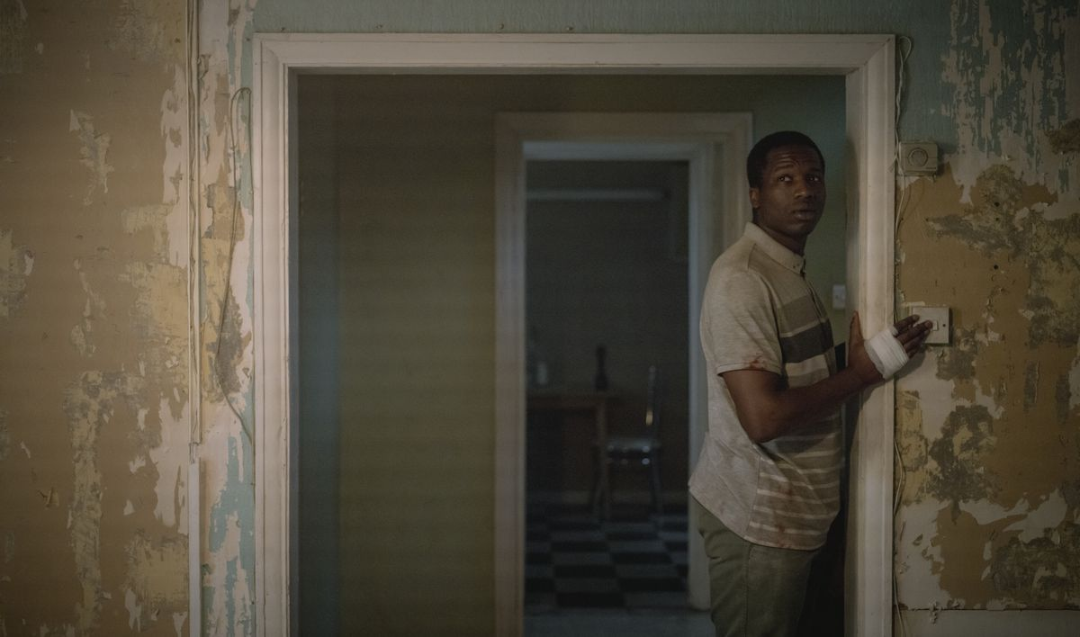 Sudanese refugee Bol (Sope Dirisu) cautiously turns on the lights in a room with ragged, peeling walls in the Netflix movie His House