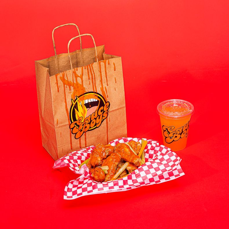 A bag with a sticker for a fake brand called Sauce Boys next to a basket of chicken wings and a clear plastic cup with another sticker for  Sauce Boys on a red backdrop.