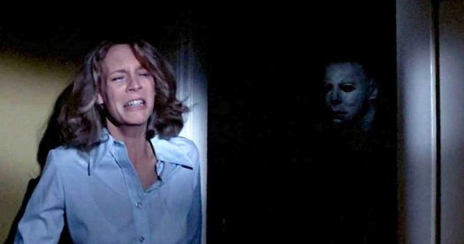 Laurie Strode (Jamie Lee Curtis) hides from a masked Michael Myers