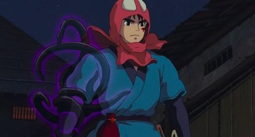 The warrior Ashitaka walks forward, his right arm writhing with the semi-translucent purple tentacles of his spirit-curse, in Princess Mononoke