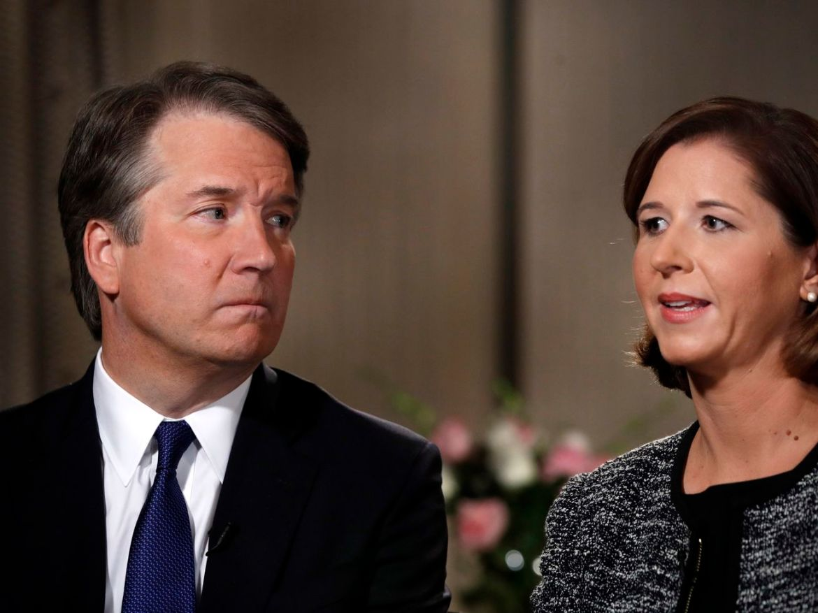 Brett Kavanaugh looks at his wife Ashley Estes Kavanaugh as they answer questions during a Fox News interview on Monday.