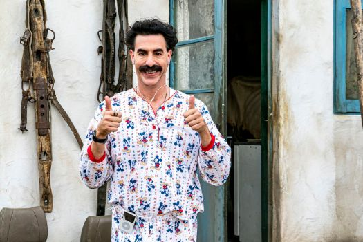 Sacha Baron Cohen as Borat, giving the thumbs-up in colorful pajamas