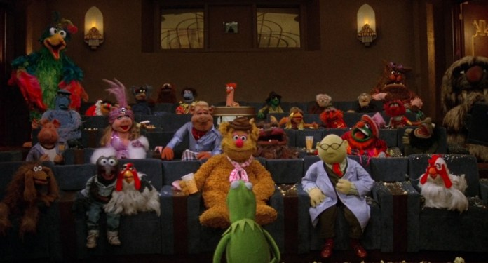The Muppet movie cast sits in a screening room with Kermit leading the conversation