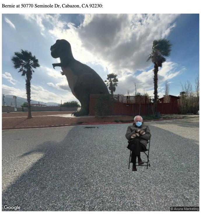 Bernie Sanders sentado em frente a uma estátua de t-rex