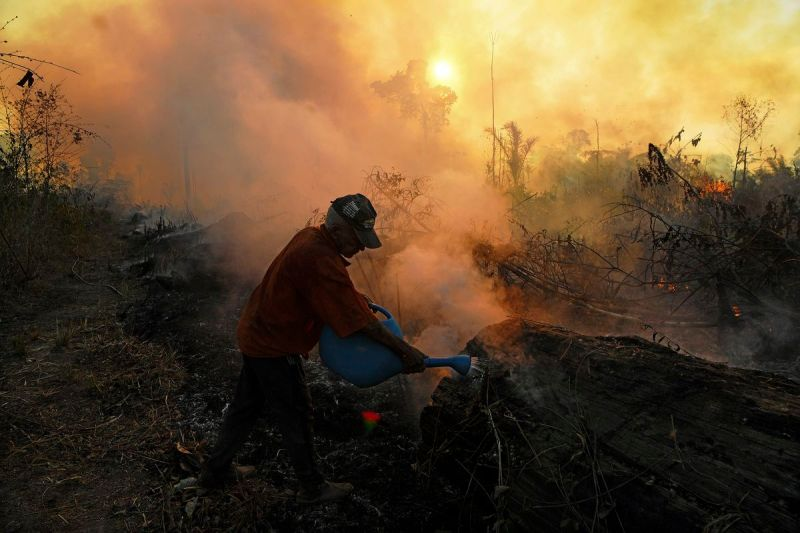 A farmer tries to pour water on an area close to an illegally lit fire in the Amazon rainforest reserve