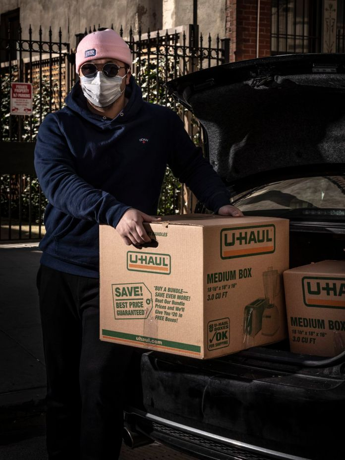 The delivery man and owner of 886 Eric Sze, wearing sunglasses and a face mask, puts a food box behind the car