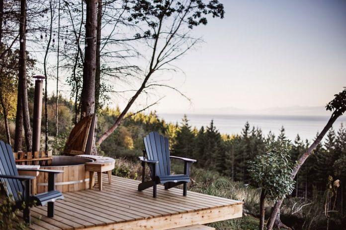 С деревянной террасы со встроенной гидромассажной ванной открывается вид на лес и воду.