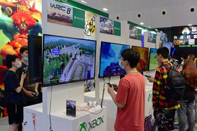 A visitor playing video games at a booth.