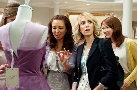 Four women examine a purple bridesmaid dress
