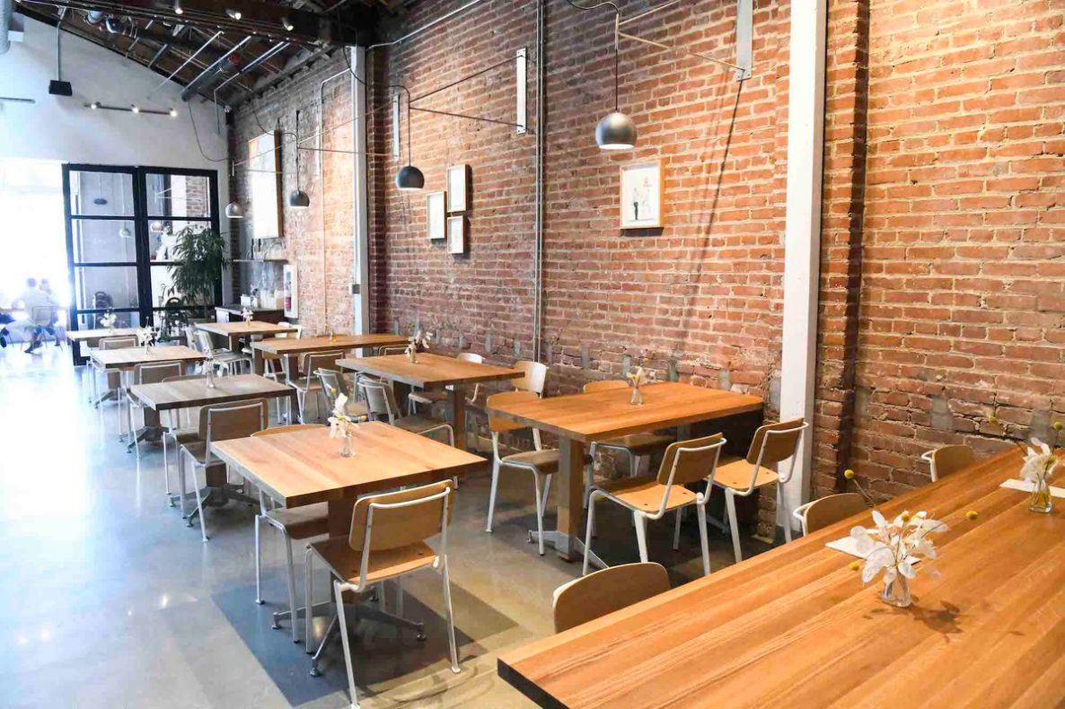 Brick walls and hanging lights over wooden tables with light streaming in.