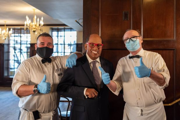 Two restaurant workers wearing gloves and masks next to a wax figure resembling journalist Al Roker