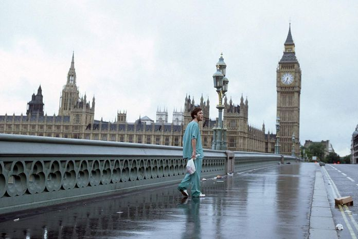 Jim (Cillian Murphy) walks down a deserted London street wearing scrubs