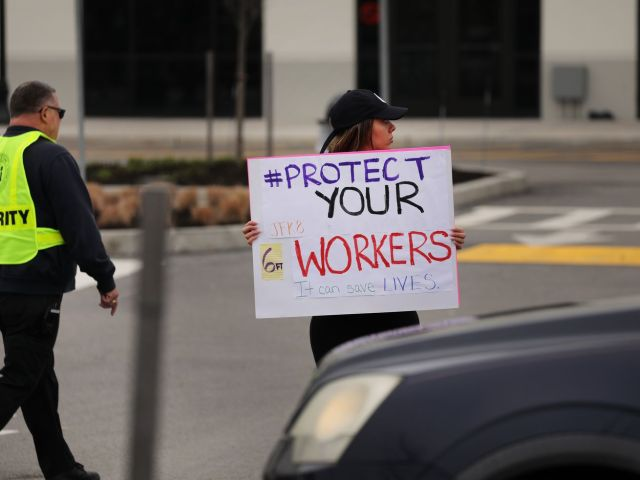 "A person standing in a parking lot holds a sign that reads ""Protect your workers."""