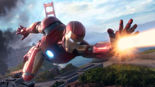 Iron Man flying with the Golden Gate Bridge in the background and firing a beam from his left hand in Marvel's Avengers