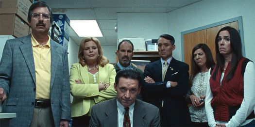 a sitting hugh jackman surrounded by other adults in bad education
