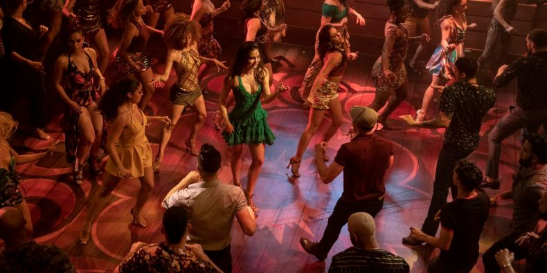 A dancer in a green dress is surrounded by other dancers in a dance club.