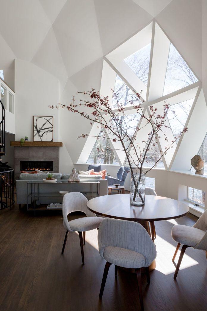 Куполообразная гостиная с серым диваном, камином и круглым обеденным столом со стульями, напротив треугольных окон.