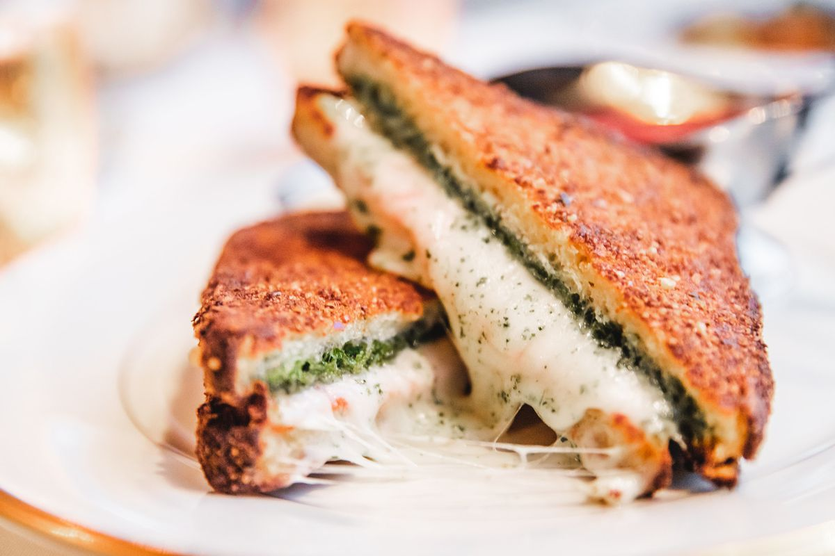 A grilled mozzarella and pesto sandwich cut in triangles stacked on top of each other, connected by strings of cheese.