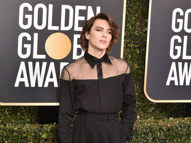 Actor Cody Fern of <em>American Horror Story: Apocalypse</em> and the <em>Assassination of Gianni Versace</em> wears a semi-sheer shirt, eye makeup, and curled hair at the 2019 Golden Globes.