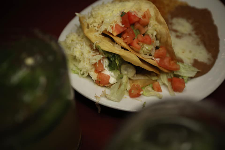 A plate of tacos with beans and rice on the side.