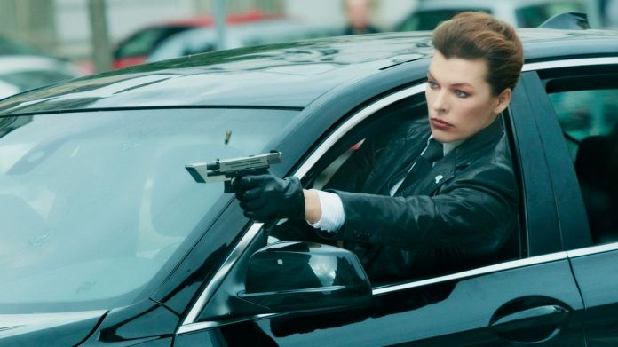 """Milla Jovovich as Special Agent """"Bruce"""" brandishing a pistol while driving a car in The Rookies"""