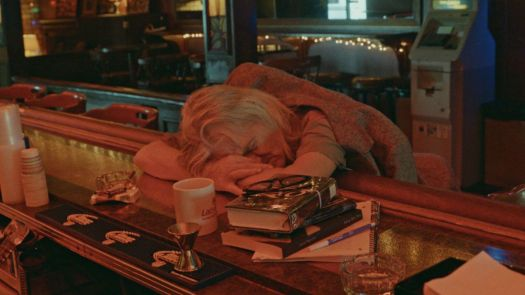 A bar patron sleeping or passed out, head down on the bar, in Bloody Nose, Empty Pockets