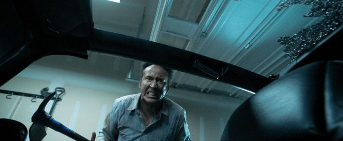 Nic Cage grimaces into a car window