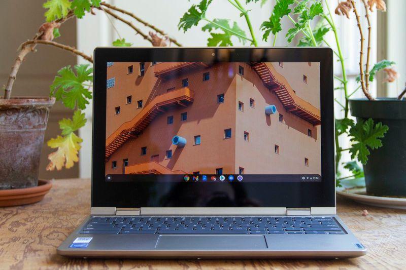 Il Chromebook Lenovo Ideapad Flex 3 è aperto su un tavolo di fronte a due piante d'appartamento.  Lo schermo mostra le finestre superiori di un grande edificio.