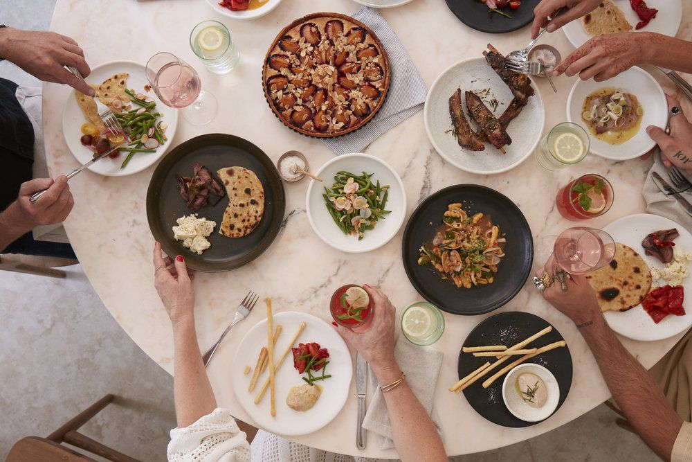 From above, a pink pastel table with diners gathered around eating from a myriad of dishes including salads, tarts, ribs, and flatbreads