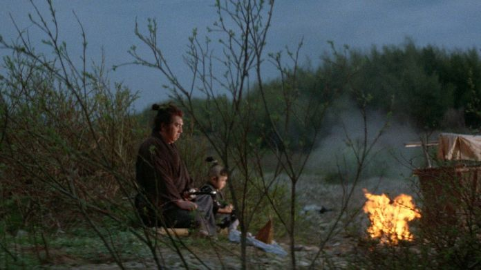 Lone Wolf and Cub sit by a fire in Lone Wolf and Cub: Baby Cart at the River Styx