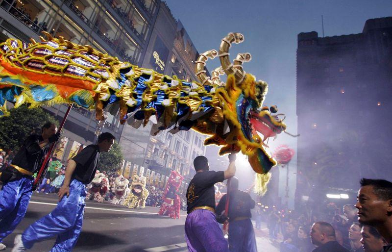 Men holding up a dragon puppet run through the streets of San Francisco.