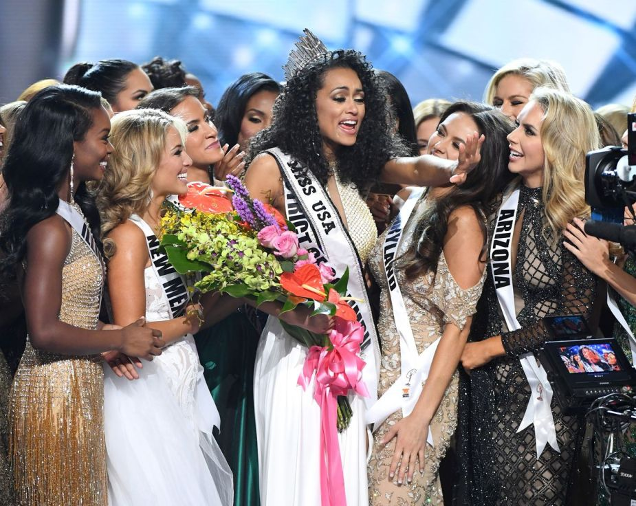 Kara McCullough, Miss District of Columbia, winning the 2017 Miss USA title surrounded by other contestants.