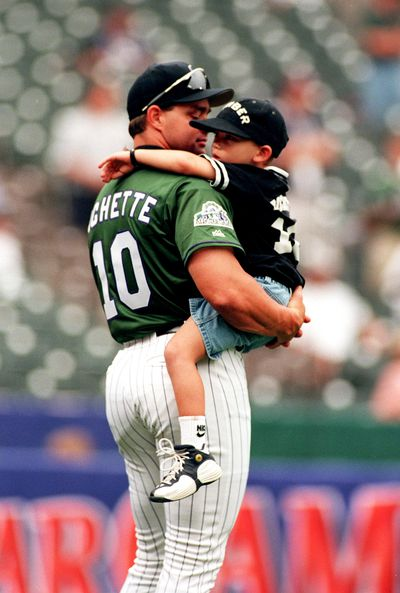 Colorado Rockies player Dante Bichette holds his son Danny during the celebrity homerun batting practice at the All Star Game.