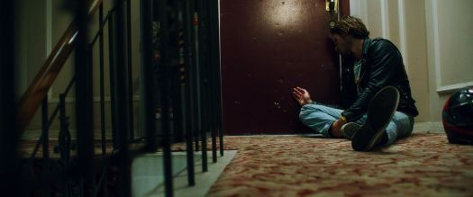 K.J. Apa sits on the floor outside of an apartment door in Songbird