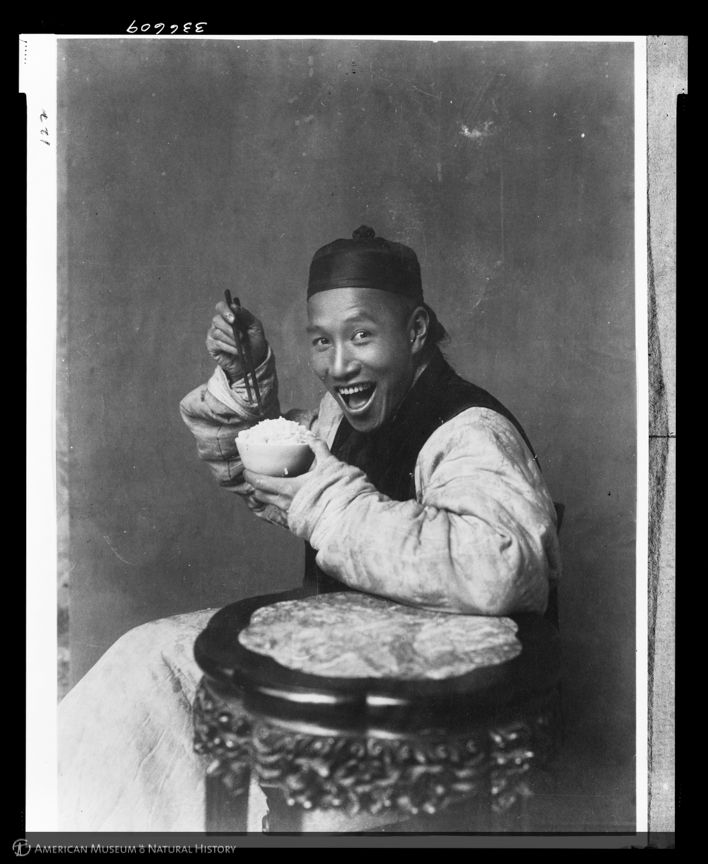 A picture from 1904 ? yes, 1904 ? of a man smiling while eating rice. (Laufer/AMNH)