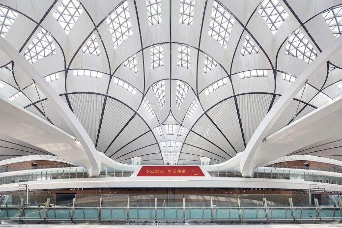 Зона выдачи багажа с тщательно продуманным белым геометрическим изгибающимся потолком.