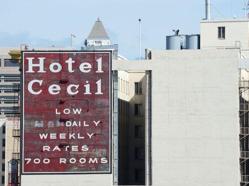 L'extérieur d'un bâtiment blanc.  Il y a un panneau rouge sur le bâtiment qui se lit comme suit: Hôtel Cecil, bas tarif journalier, tarif hebdomadaire, 700 chambres.