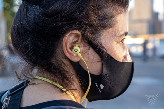 The Beats Flex, the best budget neckband wireless earbuds, pictured worn in a woman's ears.
