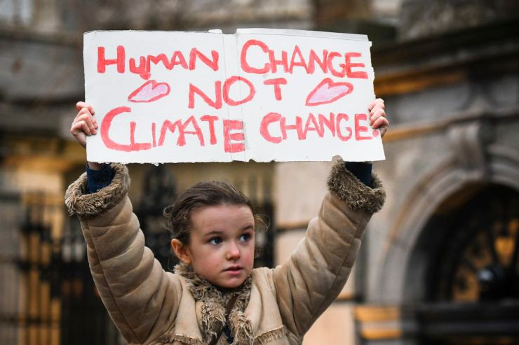 Young activist holds 'Human Change Not Climate Change' sign during a rally for climate in Dublin, Ireland.