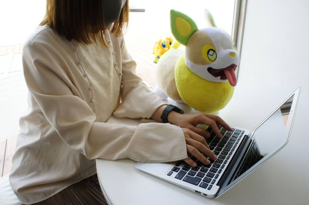 A woman works on a laptop next to a plush toy of Yamper with Joltik attached to its butt