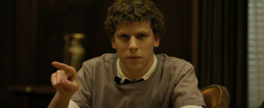 jesse eisenberg as mark zuckerberg pointing and scowling across the table during litigation in The Social Network