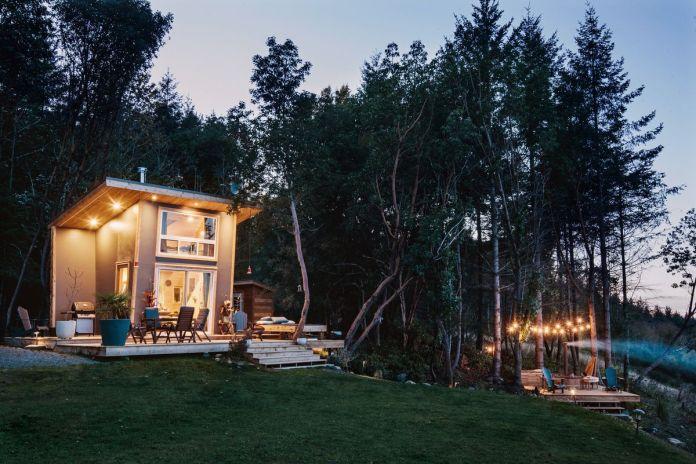 Крошечный домик с включенным светом внутри и на его крыше светится среди лесной обстановки. Отдельная палуба с гидромассажной ванной также освещена струнными лампами.