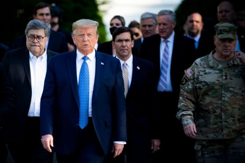 Trump in a navy suit and blue tie, walks with his cabinet—all of them in dark spots as well. Many of them appear solemn. Trump does not, squinting into the distance.