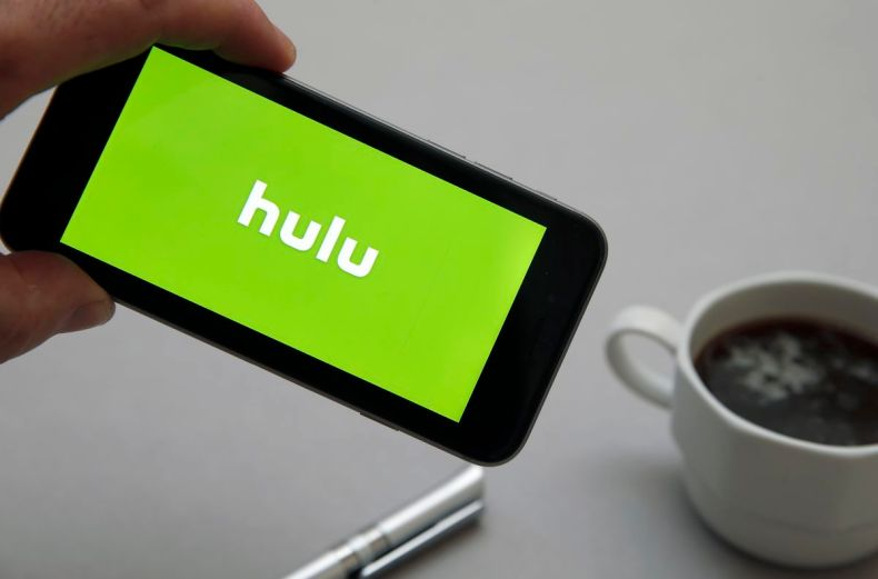 A hand holding a smartphone with the Hulu logo on its screen.