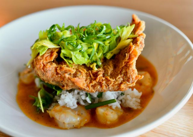 A plate of crispy red snapper served over shrimp and rice. A red sauce sits at the bottom of the bowl.