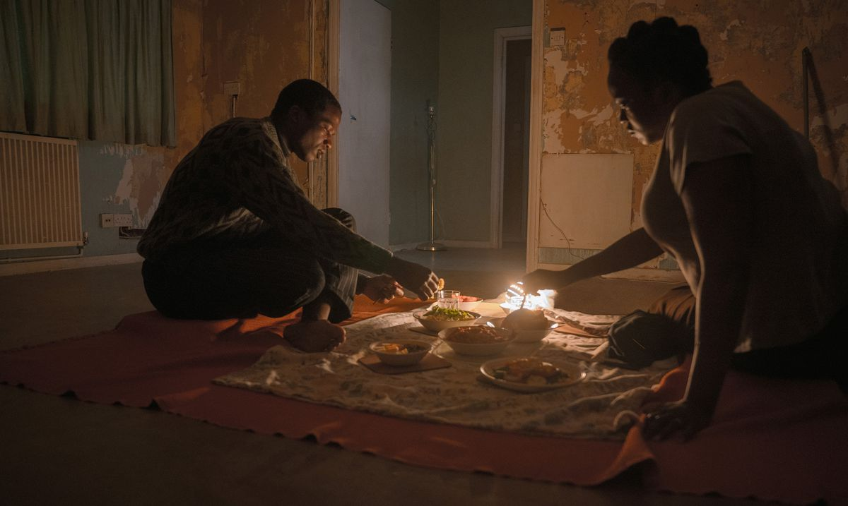 Sudanese refugees Bol (Sope Dirisu) and Rial (Wunmi Mosaku) have dinner on the floor of their unfurnished (and very haunted) row house in His House.