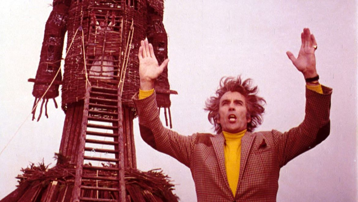 Lord Summerisle (Christopher Lee) raises his arms in front of the wicker man
