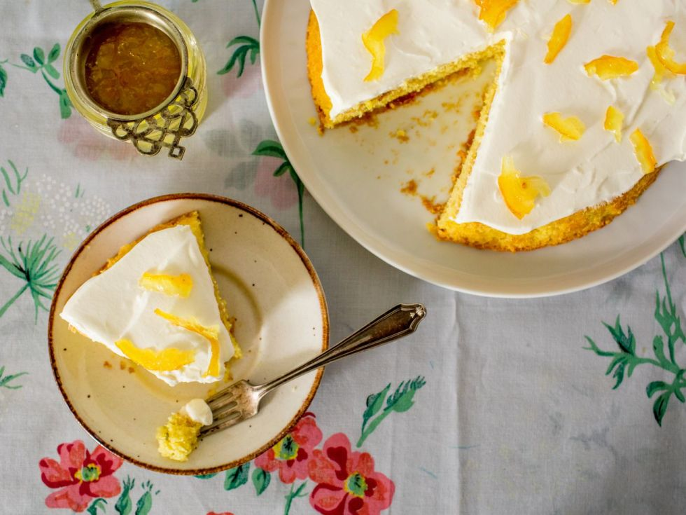 A slice of lemon-yuja cake sits on a gold-rimmed plate next to the rest of the cake and a jar of yuja tea; below it is white a tablecloth patterned with flowers.